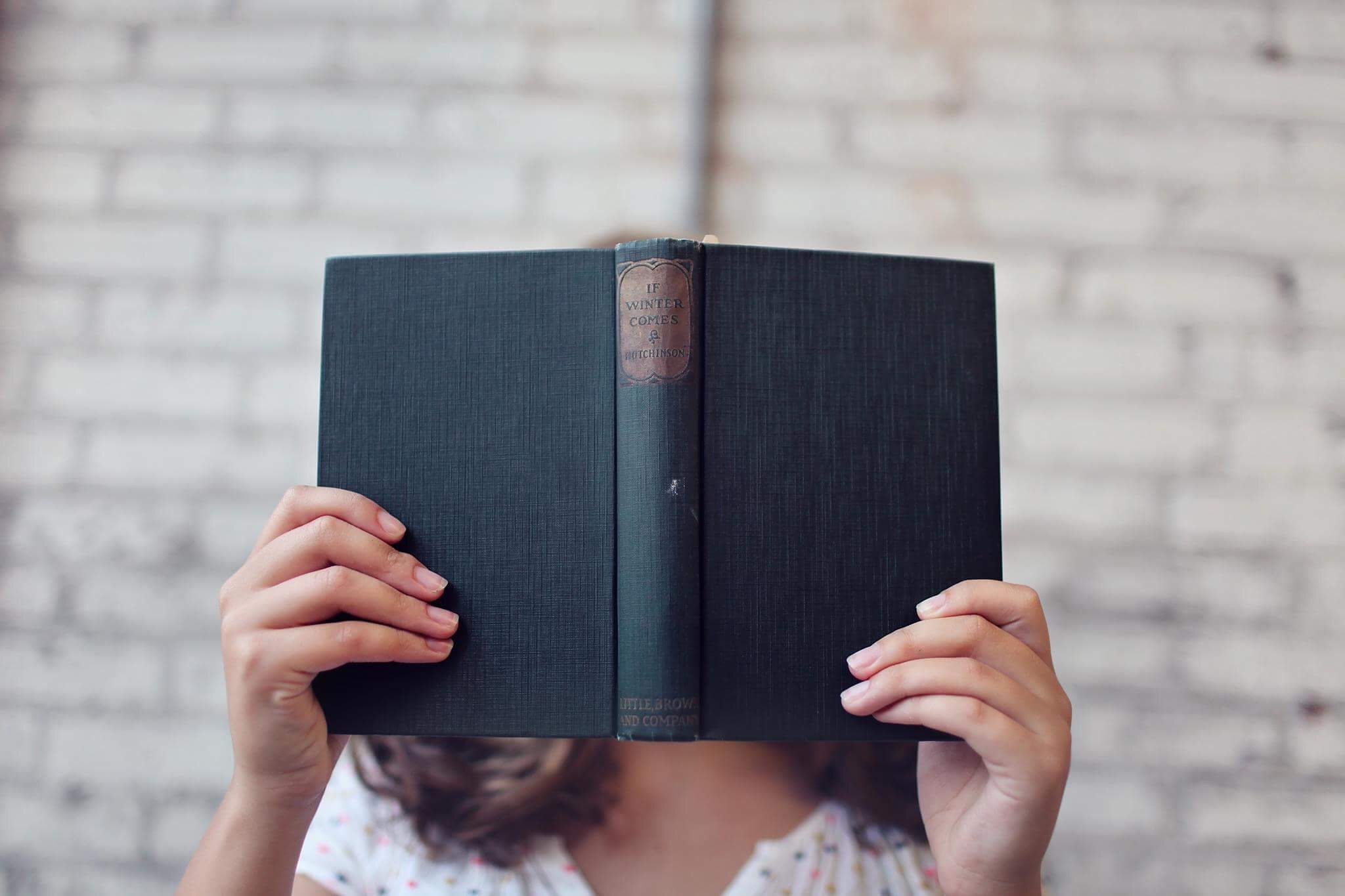woman holding a book open in front of her face